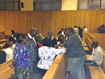 Journalist Bheki Makhubu standing in the dock talking with family and friends before this morning's hearing