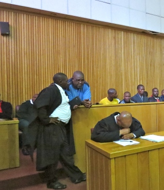 In the dock_Swazi editor Bheki Makhubu  waiting to hear his fate on bail, talking with his lawyer at Swaziland's high court on 5 Dec 2014